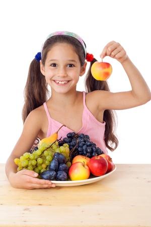 Lachend meisje met appel in de hand en plaat van vruchten, geïsoleerd op wit, geïsoleerd op wit