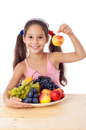Smiling girl with apple in hand and plate of fruits, isolated on white, isolated on white