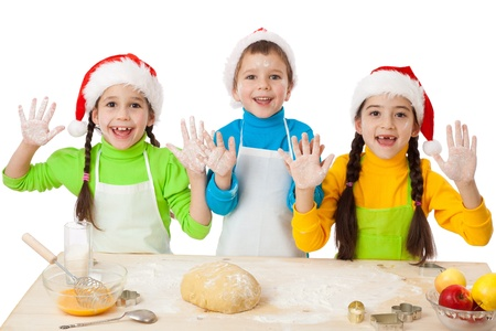 little dough: Three smiling kids with Christmas cooking and hands up sign, isolated on white Stock Photo
