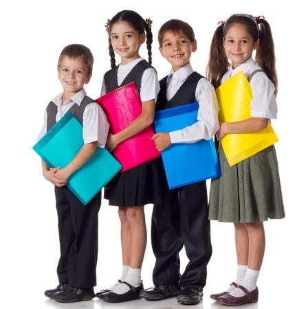 Vier lachende schoolchilds staan met kleurrijke mappen, geïsoleerd op wit Stockfoto