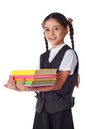 Smiling schoolgirl standing with colorful stack of books in hands, isolated on white Stock Photo - 15892329