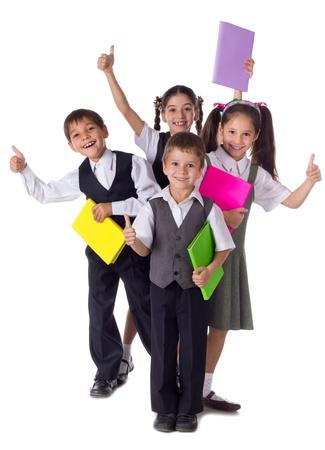 Vier lachende schoolkind staan met kleurrijke boeken en thumbs up teken, geïsoleerd op wit