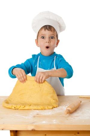 ni�os cocinando: Sorprendido muchacho poco amasando la masa, aislado en blanco