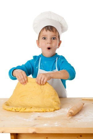 Surprised little boy kneading the dough, isolated on white