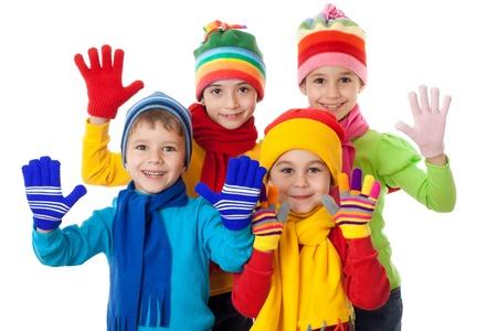 ropa de invierno: Grupo de ni�os en ropa de invierno brillante, aislado en blanco