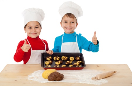 Two smiling kids with baking and thumbs up sign, isolated on white Stockfoto