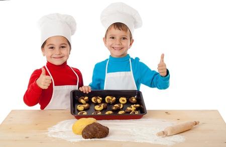 Twee lachende kinderen met bakken en thumbs up teken, geïsoleerd op wit
