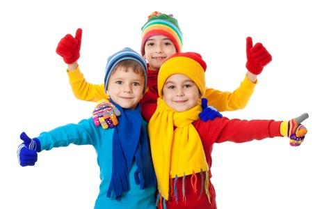 ropa invierno: Grupo de ni�os en ropa de invierno brillante y signo bien, aislado en blanco