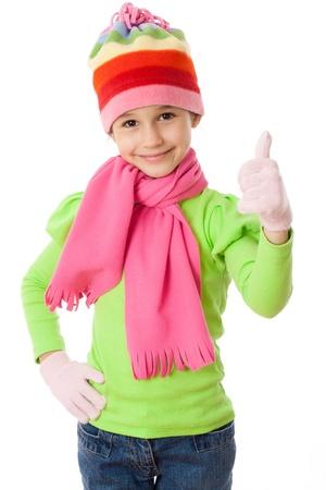 Glimlachend meisje in de winter kleding en duim omhoog teken, geïsoleerd op wit