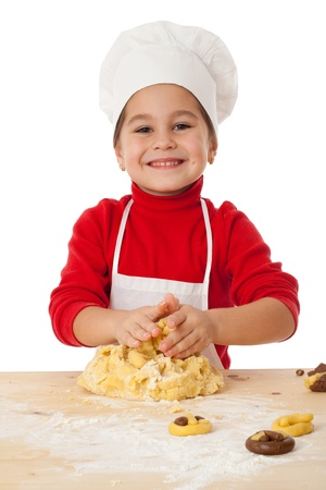 little dough: Smiling little girl kneading the dough for cookies, isolated on white Stock Photo