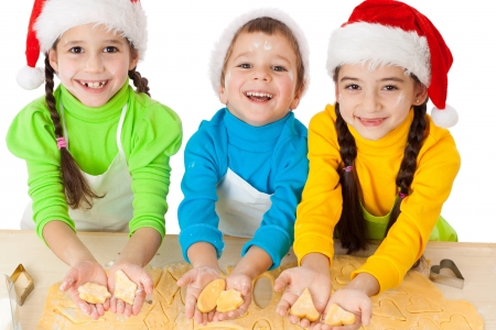 christmas cookie: Three smiling kids showing dough for Christmas cooking, isolated on white