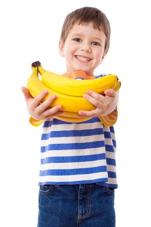 Happy jongen strekt zich uit vóór een tros bananen, geïsoleerd op wit Stockfoto