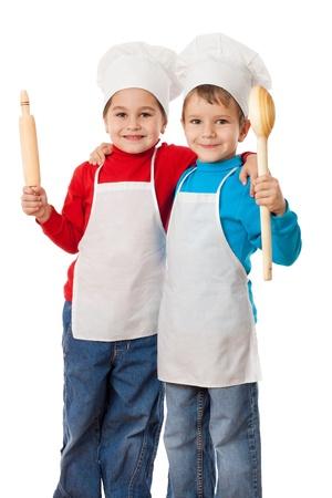 ni�os cocinando: Dos cocineros sonrientes peque�os con cuchara y rodillo, aislado en blanco