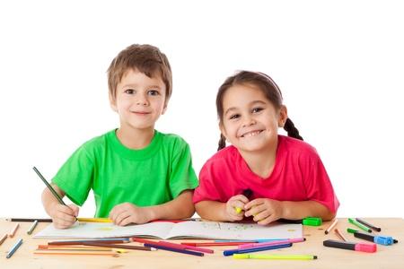 niños estudiando: Dos pequeños niños sonrientes en el sorteo mesa con lápices de colores, aislados en blanco