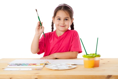 watercolour paintbrush: Inspired little girl with paintbrush and watercolors at the table, isolated on white