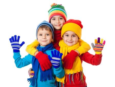 ropa de invierno: Grupo de tres ni�os en ropa de invierno brillante, aislado en blanco