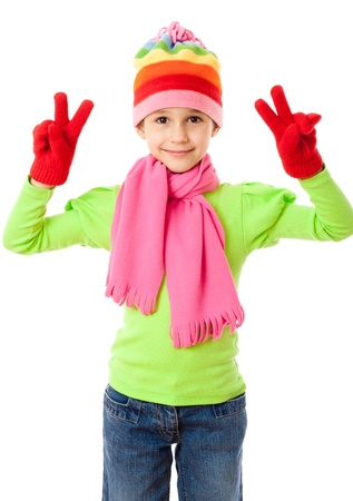 Funny girl in winter clothes with victory sign, isolated on white photo