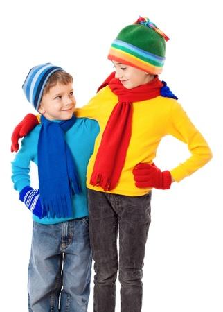 Twee lachende kinderen in de winter kleding staan samen, geïsoleerd op wit Stockfoto