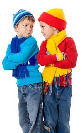 Two quarreling kids in winter clothes, isolated on white