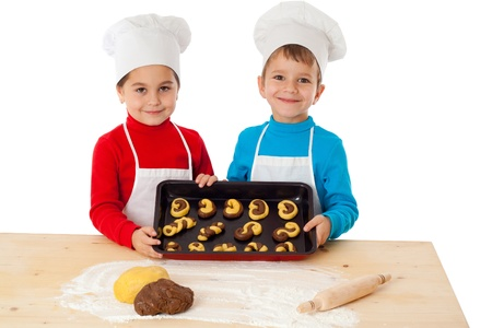 Two smiling kids with baking on oven-tray, isolated on white photo