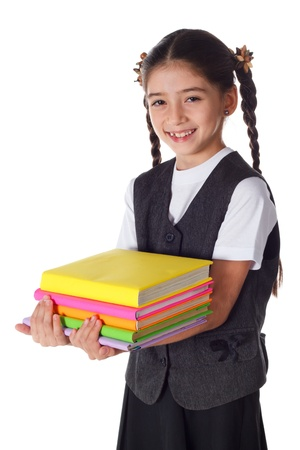 Smiling schoolgirl standing with colorful stack of books in hands, isolated on white Stock Photo - 16985376
