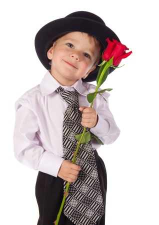 Little boy in hat and necktie standing with red rose, isolated on white