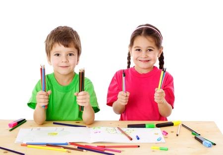 Twee lachende kleine kinderen aan de tafel met kleurpotloden, geïsoleerd op wit