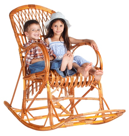 Two funny kids sitting in the rocking chair together, isolated on white photo