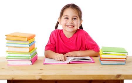 Smiling girl reading the books on the desk, isolated on white Stock Photo - 17458413