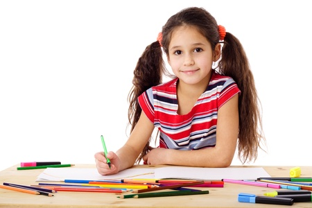 Smiling girl at the table drawing in the notebook, isolated on white Stock Photo - 17458415