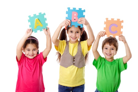 Three kids with colorful letters in raised hands, isolated on white Stock Photo - 17543655
