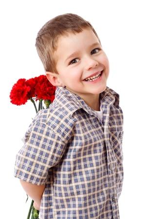 Lachende jongen verbergen van een boeket van rode anjers achter zich, geïsoleerd op wit Stockfoto