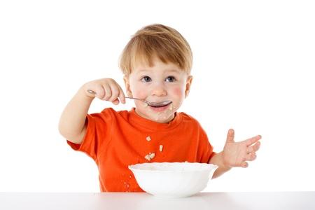 Baby die leert om zichzelf te voeden - het eten van de havermout met een lepel, geïsoleerd op wit Stockfoto