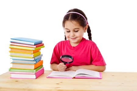 Smiling girl reading the books on the desk with magnifying glass, isolated on white Stock Photo - 17669520