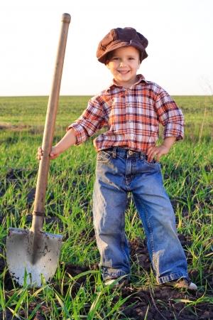 Lachende jongen met schop in het veld