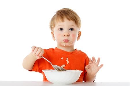 Kleine jongen leren om zichzelf te voeden - het eten van de havermout met een lepel uit een kom, geïsoleerd op wit Stockfoto