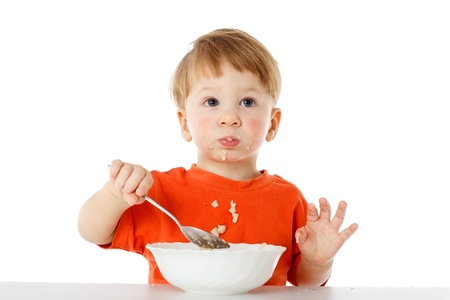 Little boy learning to feed herself - eating the oatmeal with a spoon from a bowl, isolated on white Stock Photo