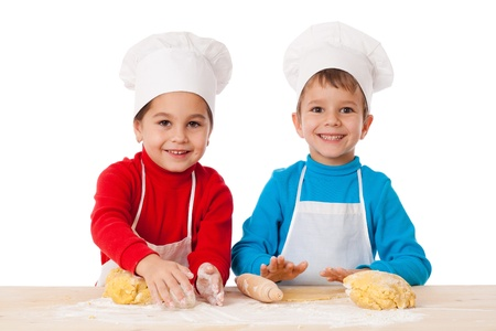 Two kids kneading the dough together, isolated on white photo