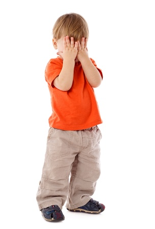 Little boy hide face under hands, playing hide-and-seek, isolated on white Stockfoto