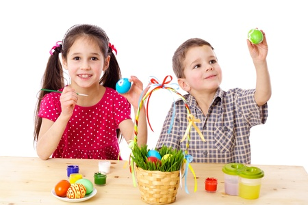 Two smiling kids paint easter eggs, isolated on white