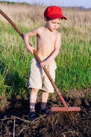 rake: Little boy works with garden rake in the field Stock Photo