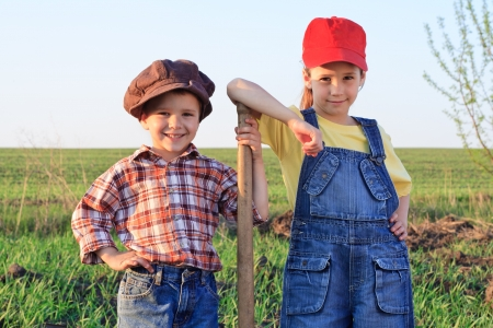 Two kids standing in field with shovel