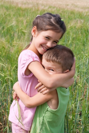 Two children embracing in a wheat field photo