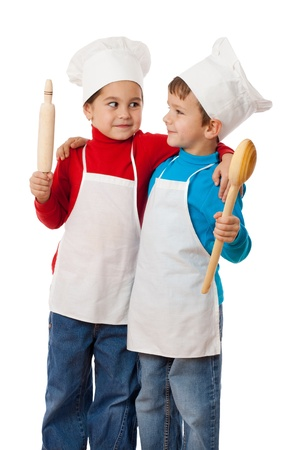 Two smiling little cooks with ladle and rolling pin, cuddling together, isolated on white photo