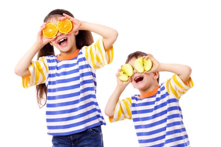 citrus family: Two funny kids with fruits on eyes, isolated on white