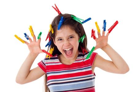 Ni�a enfadada con pinzas de la ropa en los dedos, aislado en blanco photo