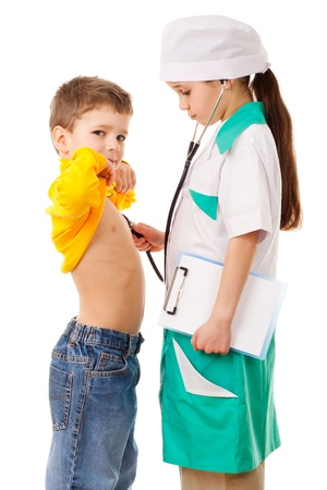 Little girl in doctor costume do listening a boy s lungs, playing with stethoscope, isolated on white photo