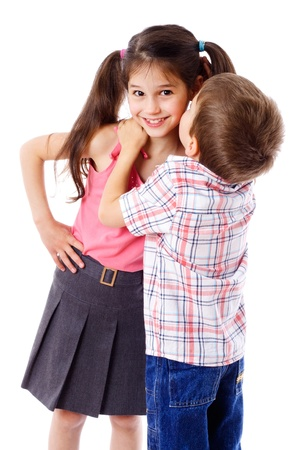 Little boy whispering something to smiling girl, isolated on white photo