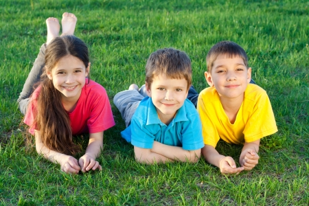 Group of happy kids lying on the green grass field photo