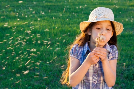 Girl in a hat blowing to dandelion, standing on a green meadow photo